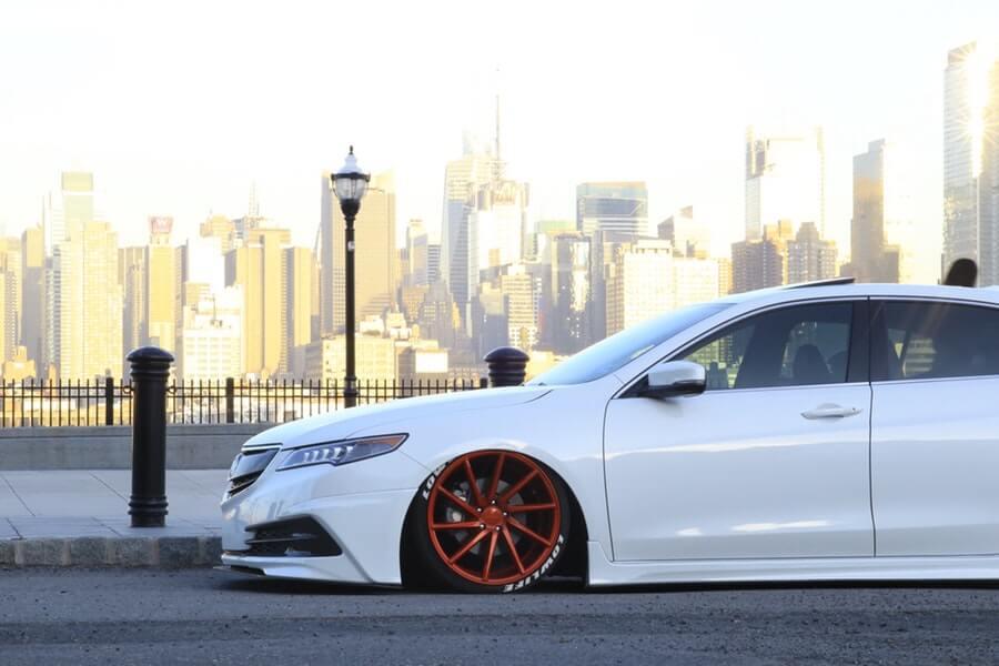 Custom lowered white Acura with body kit and orange rims.