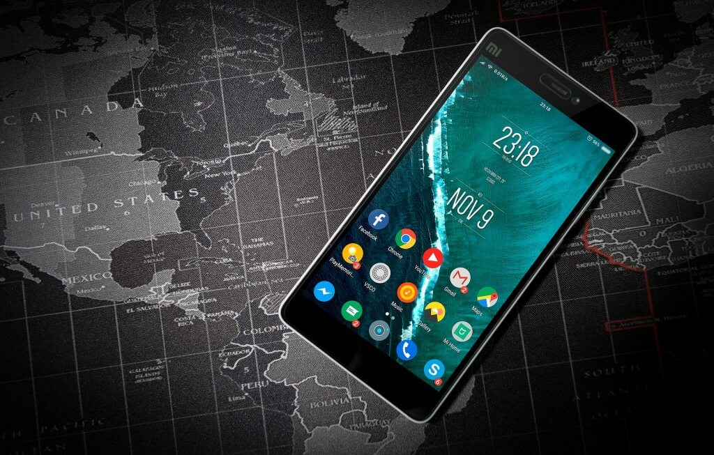 Android tablet with apps, on top of black and white world map.