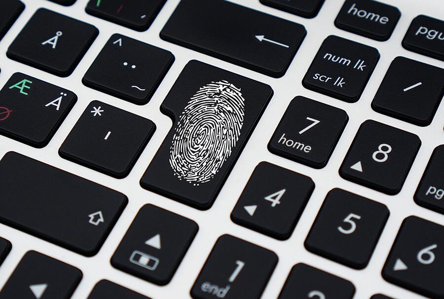 Keyboard with fingerprint on enter/return key, symbolizing digital/online security.