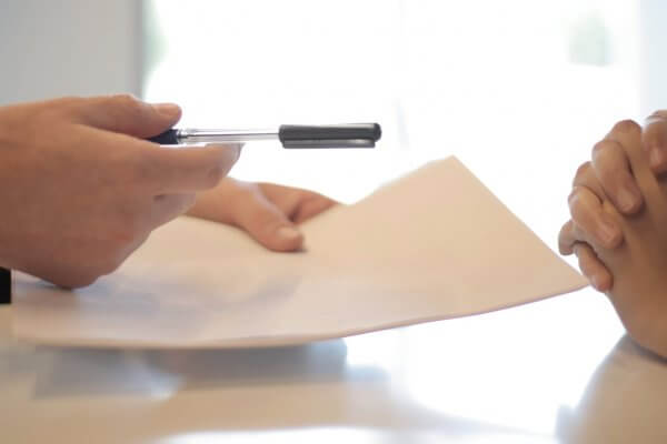 Offering a pen to sign a contract to someone who is pensative with closed hands.